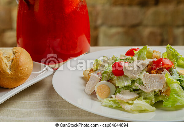 Fresh caesar salad in a white plate on the table. - csp84644894