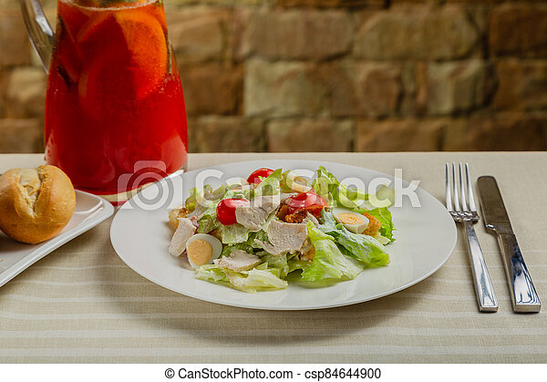 Fresh caesar salad in a white plate on the table. - csp84644900