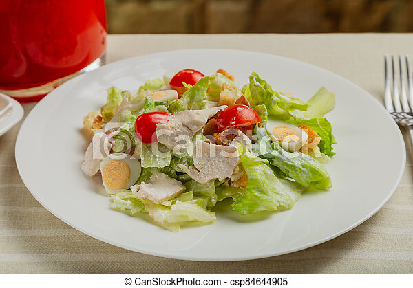 Fresh caesar salad in a white plate on the table. - csp84644905