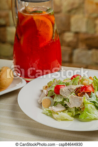 Fresh caesar salad in a white plate on the table. - csp84644930