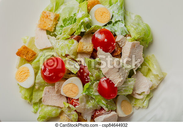 Fresh caesar salad in a white plate on the table. - csp84644932