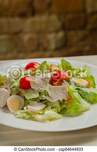 Fresh caesar salad in a white plate on the table. - csp84644933