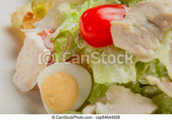 Fresh caesar salad in a white plate on the table. - csp84644938
