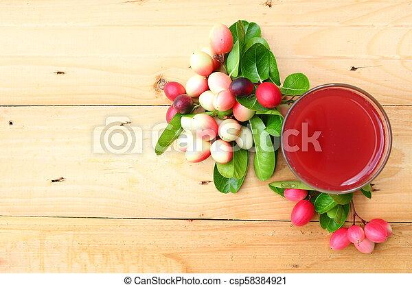 Fresh carissa carandas juice on wooden background - csp58384921