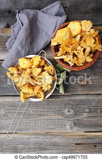 Fresh chanterelle mushrooms on a wooden background - csp49971703