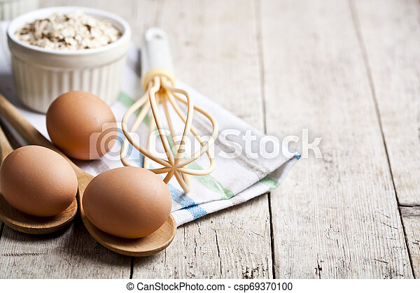 Fresh chicken eggs, oat flakes in ceramic bowl and kitchen utensil on rustic wooden table background. - csp69370100