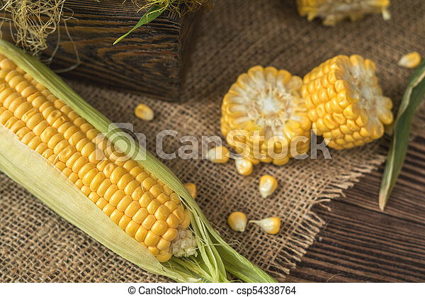 Fresh corn on cobs on rustic wooden table, top view. Dark wooden background freshly harvested organic corn. - csp54338764