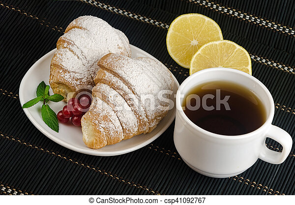 fresh cup of hot black coffee with croissants and lemon - csp41092767