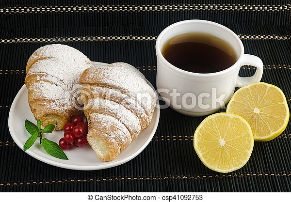 fresh cup of hot black coffee with croissants and lemon - csp41092753