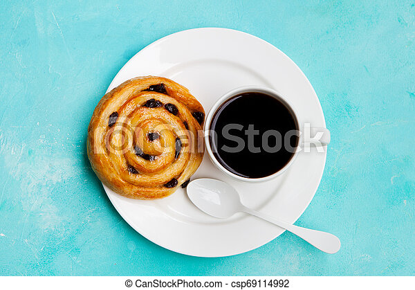 Fresh danish pastry with raisins and cup of black coffee on blue background. Top view. Copy space. - csp69114992