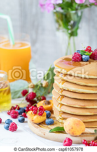 Fresh delicious pancakes with summer berries on light background. - csp61057978
