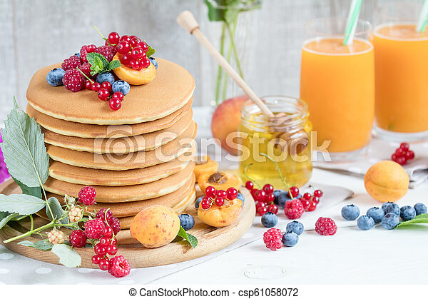 Fresh delicious pancakes with summer berries on light background. - csp61058072