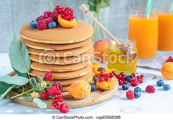 Fresh delicious pancakes with summer berries on light surface - csp63568388