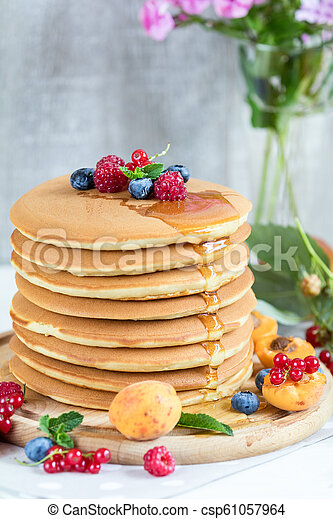 Fresh delicious pancakes with summer berries on light background. - csp61057964