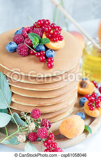 Fresh delicious pancakes with summer berries on light background. - csp61058046