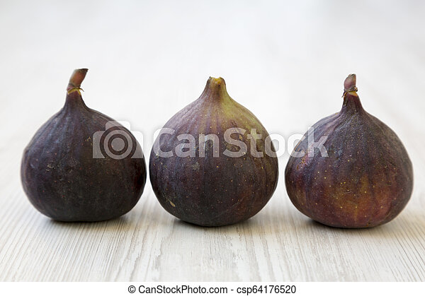 Fresh figs on a white wooden background, side view. Close-up. - csp64176520