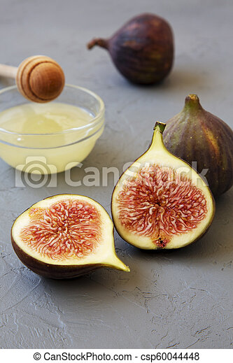 Fresh figs with honey on gray background, side view. Close-up. - csp60044448