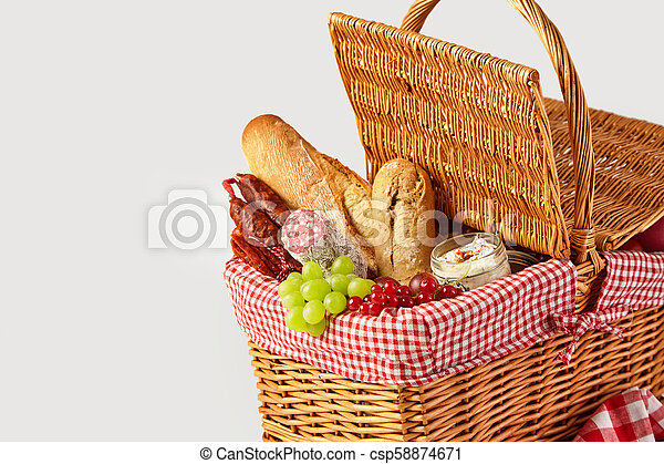Fresh fruit, bread and cheese in a picnic basket - csp58874671