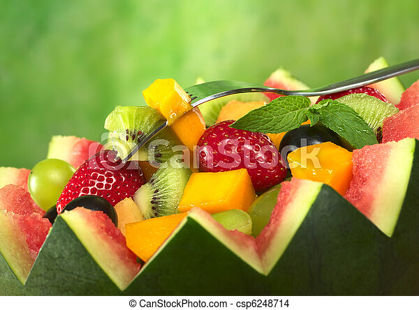 Fresh fruit salad (strawberry, kiwi, mango, grape) in melon bowl with kiwi and mango on fork and a mint leaf as garnish in front of green background (Selective Focus, Focus on the fruit on the fork an - csp6248714
