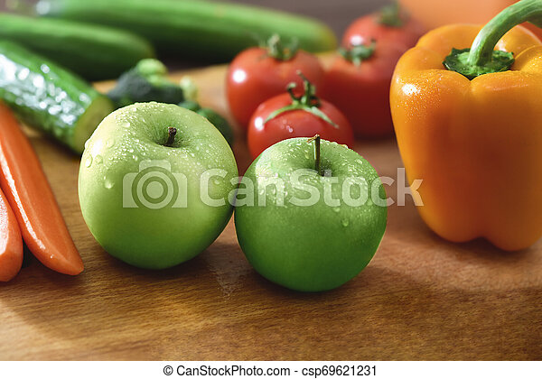 Fresh fruits and vegetables on the old wooden board - csp69621231