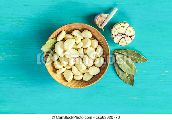 Fresh garlic heads, cloves set on a blue turquoise wooden surface - csp63620770