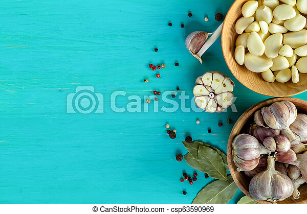 Fresh garlic heads, cloves set on a blue turquoise wooden surface, copy space - csp63590969