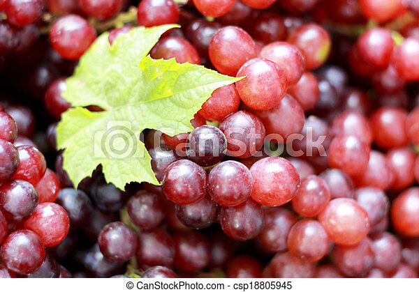 Fresh grapes with green leaves on a background. - csp18805945