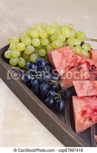 Fresh green and blue grapes, with pieces of watermelon - csp87997416