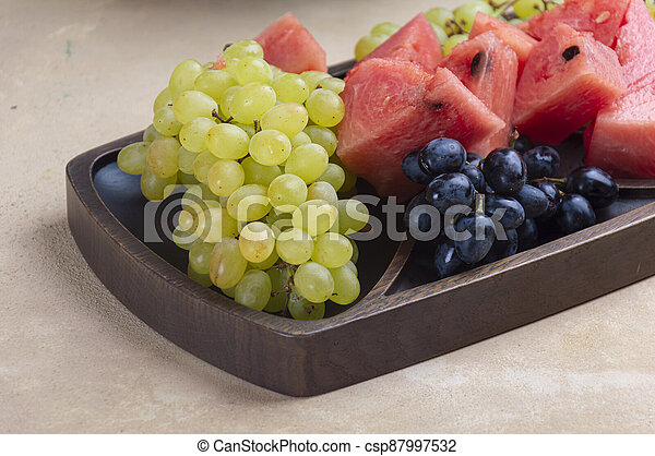Fresh green and blue grapes, with pieces of watermelon - csp87997532