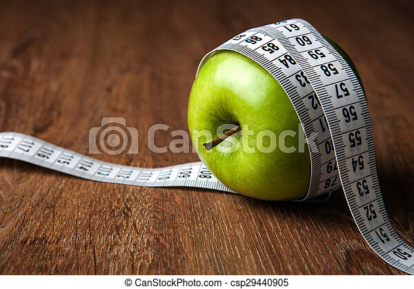 fresh green apple on a wooden table with measure - csp29440905