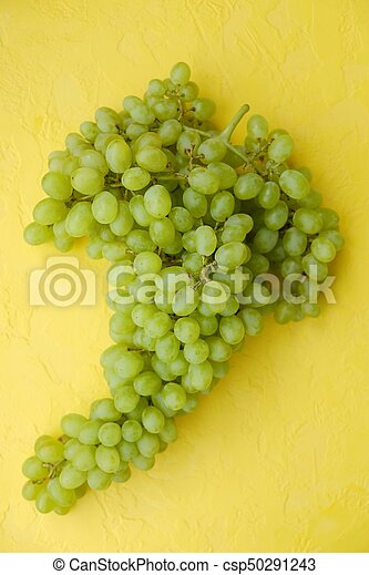 Fresh green grapes on a yellow background - csp50291243