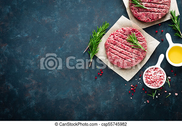 Fresh minced beef meat burgers with spices on dark background. Raw ground beef meat. Flat lay. Top view - csp55745982