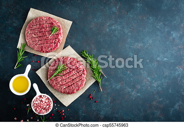 Fresh minced beef meat burgers with spices on dark background. Raw ground beef meat. Flat lay. Top view - csp55745963