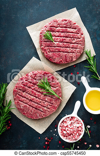 Fresh minced beef meat burgers with spices on dark background. Raw ground beef meat. Flat lay. Top view - csp55745450