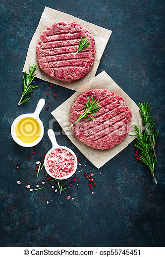 Fresh minced beef meat burgers with spices on dark background. Raw ground beef meat. Flat lay. Top view - csp55745451
