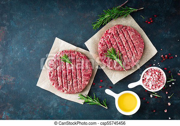 Fresh minced beef meat burgers with spices on dark background. Raw ground beef meat. Flat lay. Top view - csp55745456