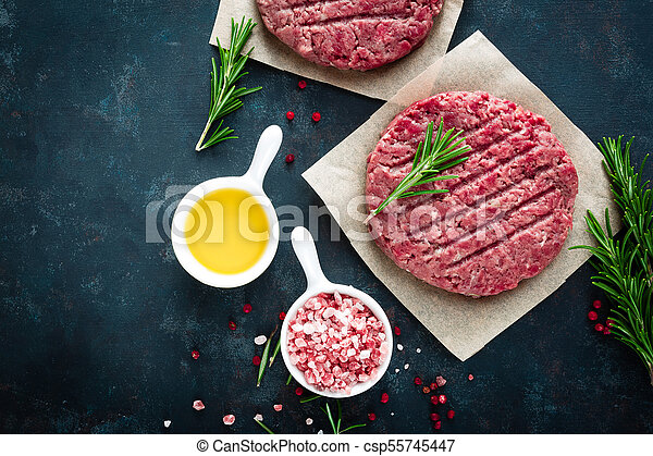 Fresh minced beef meat burgers with spices on dark background. Raw ground beef meat. Flat lay. Top view - csp55745447