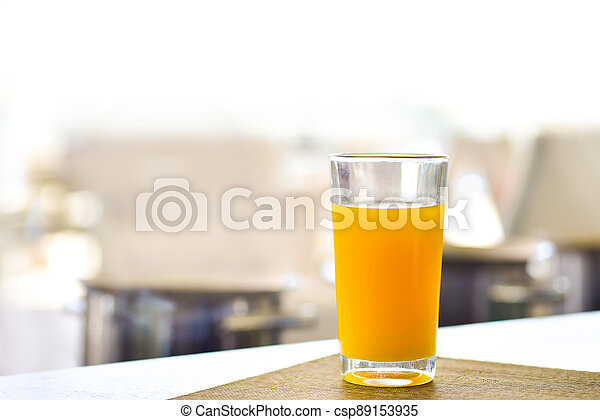 Fresh orange juice in a glass on the table - csp89153935