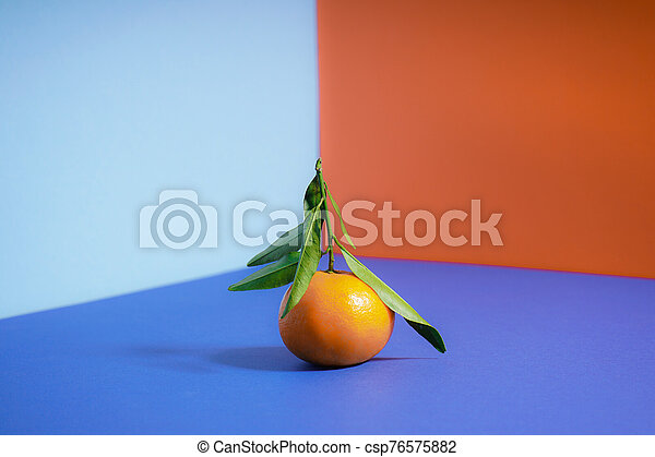 Fresh orange mandarin with green leaves, on a colorful background. - csp76575882