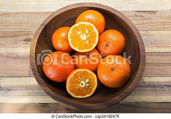 Fresh oranges in wooden bowl. On a wooden background. - csp34192478