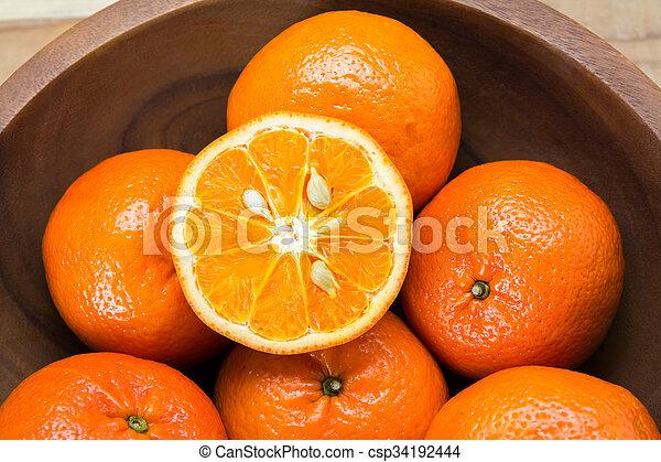 Fresh oranges in wooden bowl. On a wooden background. - csp34192444
