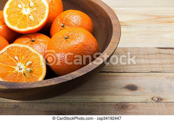 Fresh oranges in wooden bowl. On a wooden background. - csp34192447