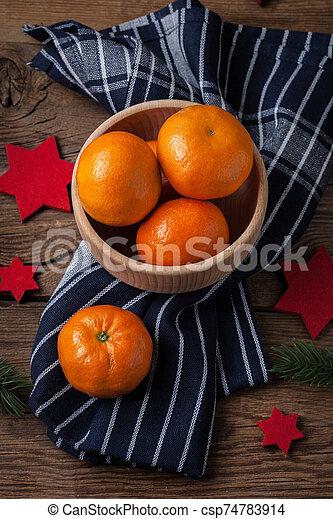 Fresh oranges in wooden bowl. - csp74783914