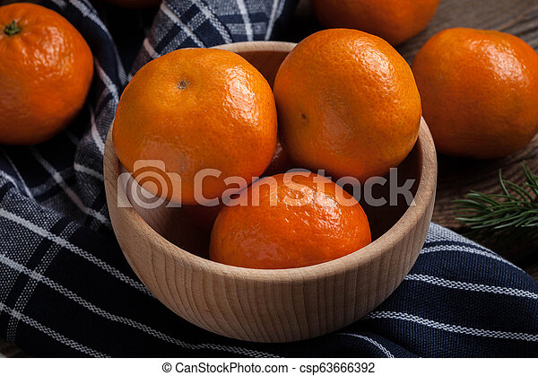 Fresh oranges in wooden bowl. - csp63666392