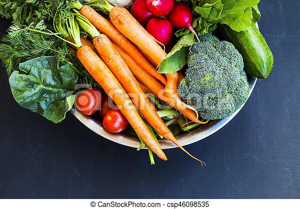 Fresh organic vegetables bowl with carrots, cauliflower, broccoli, tomatoes, mushrooms, radishes on wooden board - csp46098535