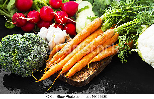 Fresh organic vegetables bowl with carrots, cauliflower, broccoli, tomatoes, mushrooms, radishes on wooden board - csp46098539