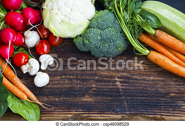 Fresh organic vegetables with carrots, cauliflower, broccoli, tomatoes, mushrooms, radishes on wooden board - csp46098529