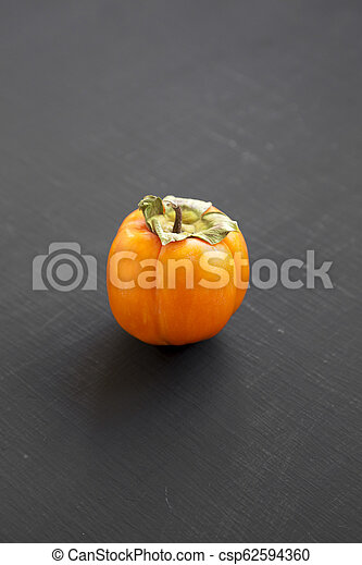 Fresh persimmon on black background, side view. Close-up. - csp62594360