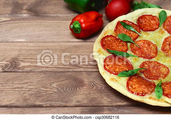 fresh pizza margarita on a wooden plate  - csp30682116