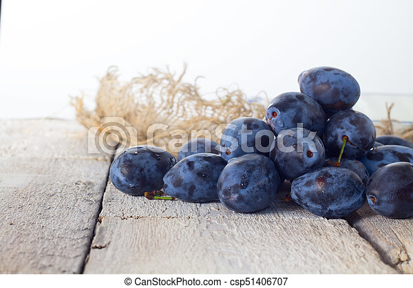 Fresh plums in basket on white background. - csp51406707